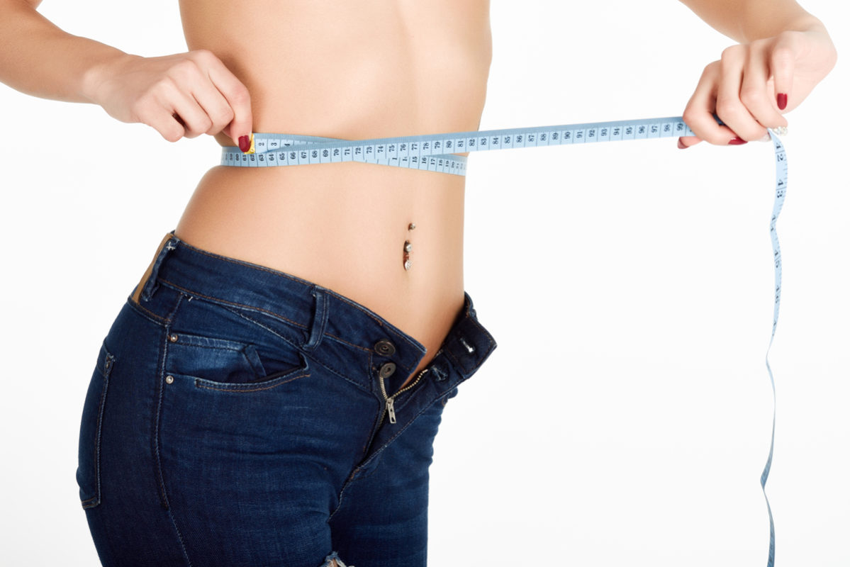 Young woman measuring waist with a tape. Fit and healthy girl with blue jeans on white background.